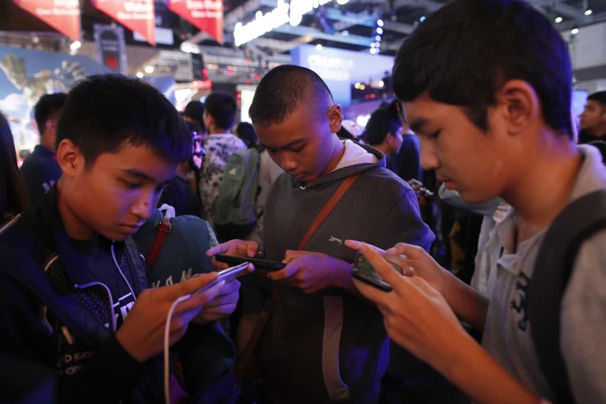 Pojat pelaavat mobiilipelejä pelitapahtumassa Bangkokissa 2019.