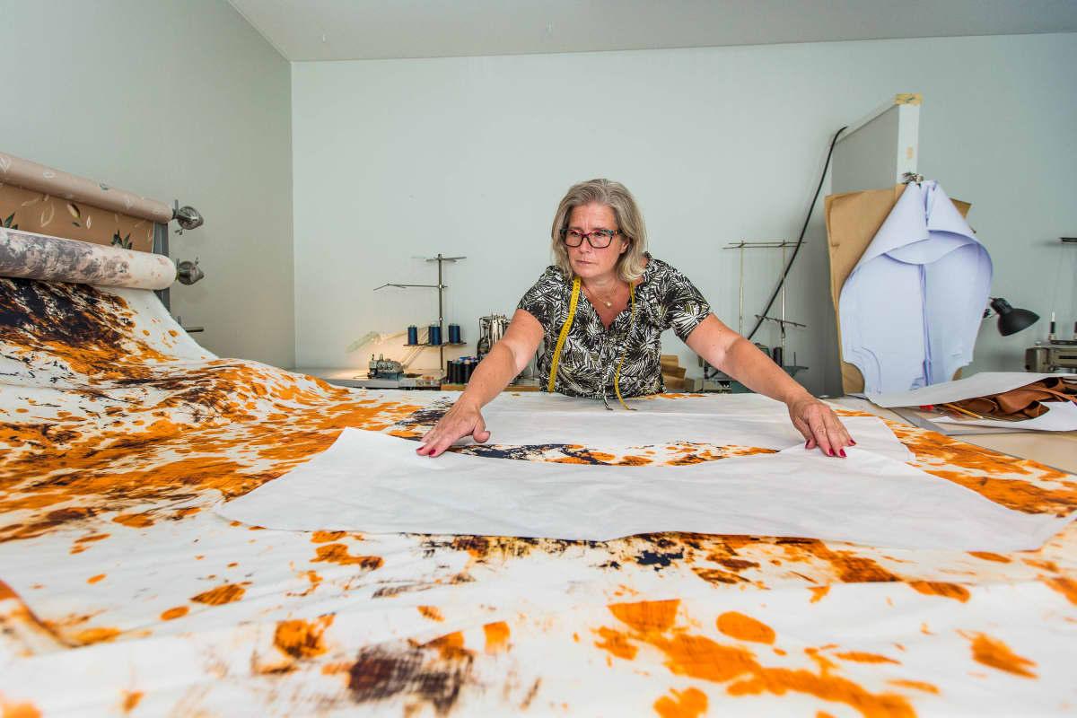Anne Äikäs mittaa kaavoilla kangasta työhuoneellaan.