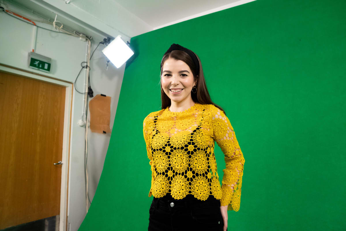Jasmin Beloued katsoo kameraan studiossa.