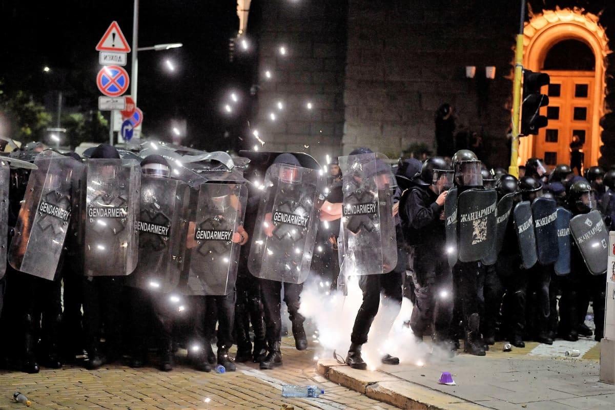 Sähikäinen räjähtää mellakkapoliisien jaloissa, Kipinät lentävät yöllisessä maisemassa. Mellakkapoliisit seisovat rivissä parlamenttirakennuksen edessä.