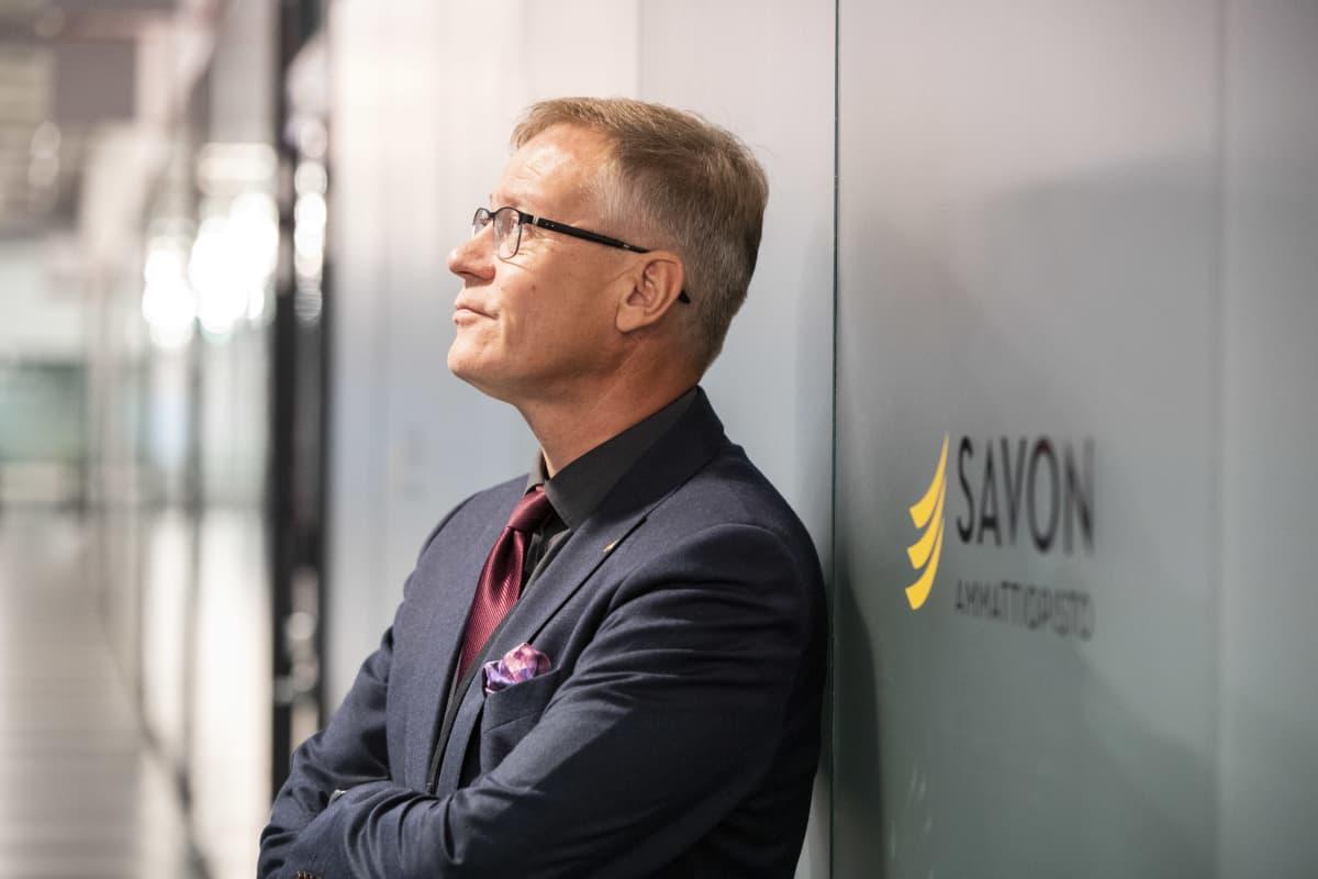 Savon koulutuskuntayhtymän johtaja Heikki Helve nojaa seinään ja katsoo ylöspäin.