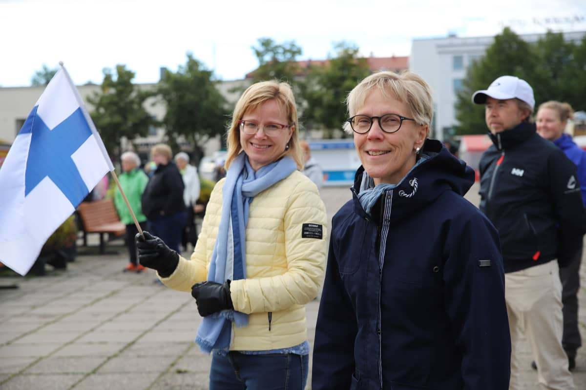 Teija Pääkkönen ja Tuula Rajaniemi seisovat Kokkolan torilla Suomen lippu kädessä