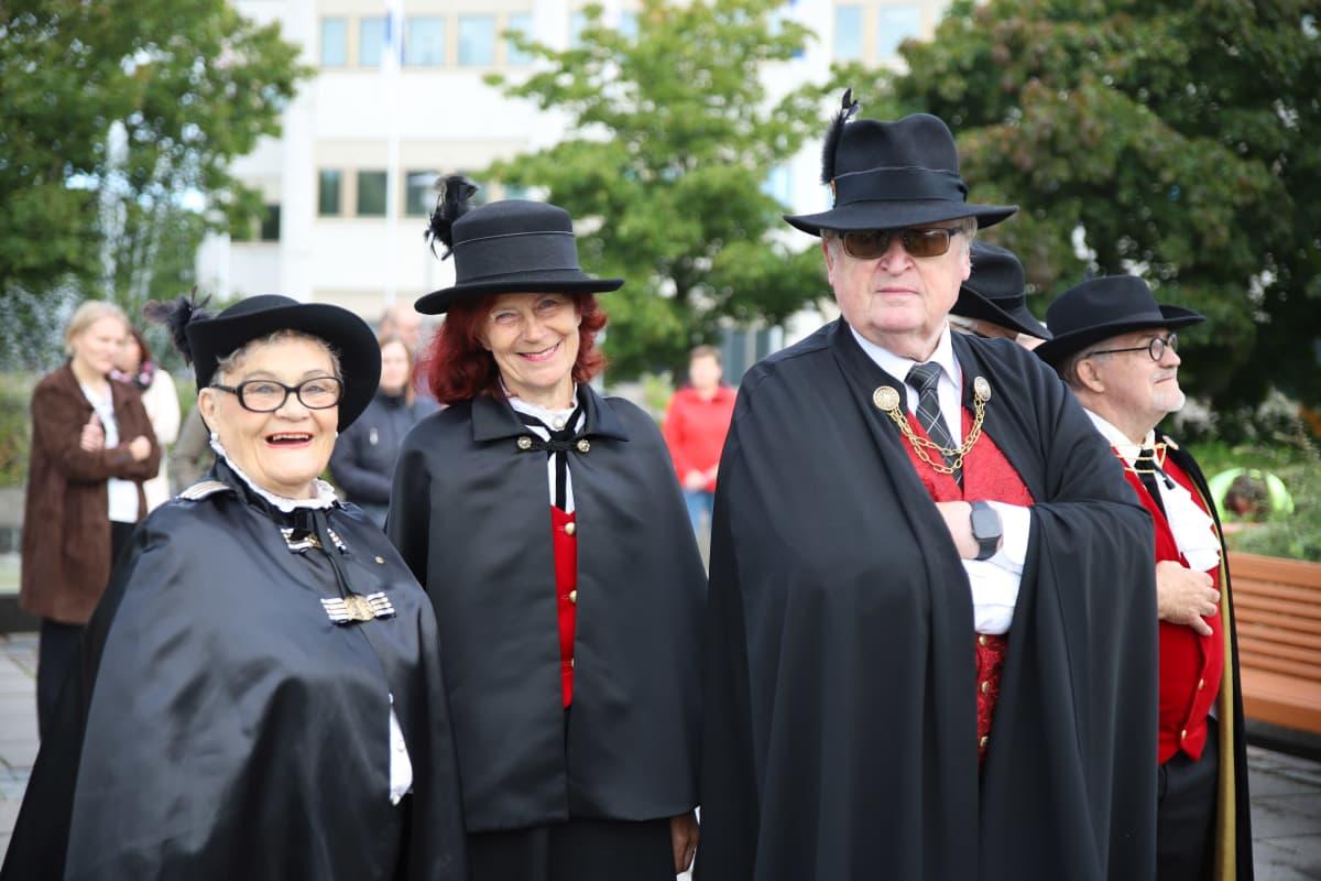 Kolme emeritus wanhaa Kallea seisoo juhla-asuissa Kokkolan torilla