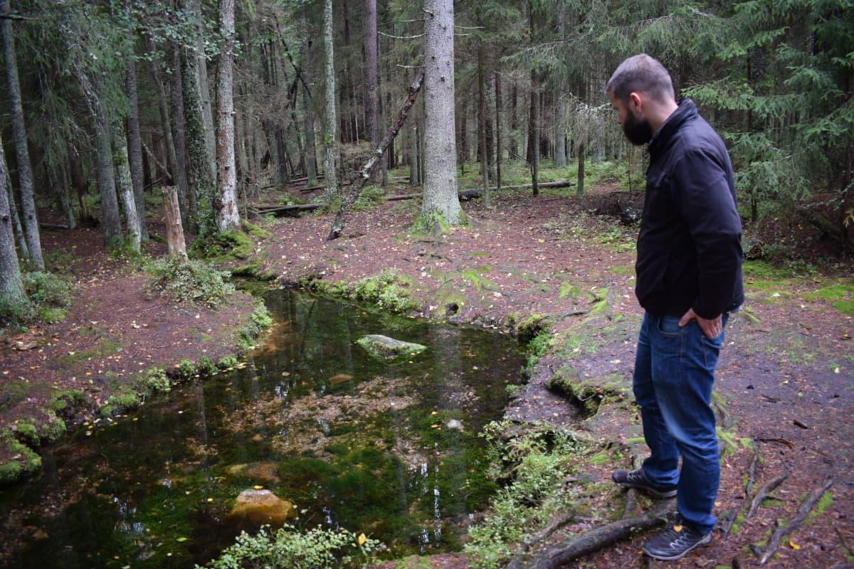 Väitöstutkija John Björkman katsoo Somerojan lähdettä Halikossa.