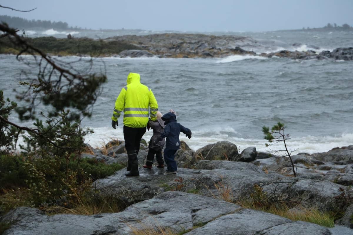 En pappa med två barn går på klippor i hård vind. Vattnet slår mot klipporna.