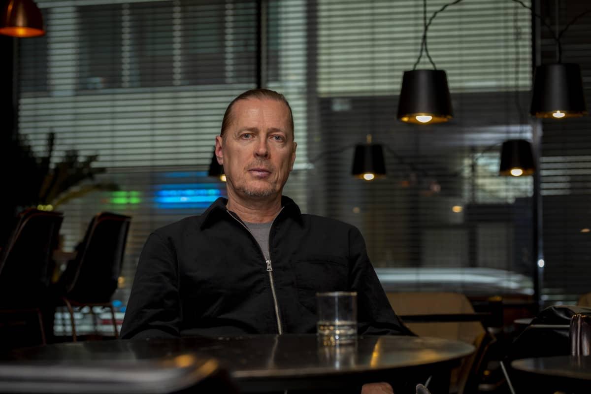 Koreografi Ismo-Pekka Heikinheimo istuu baarissa ja katsoo pöydän yli kameraan.