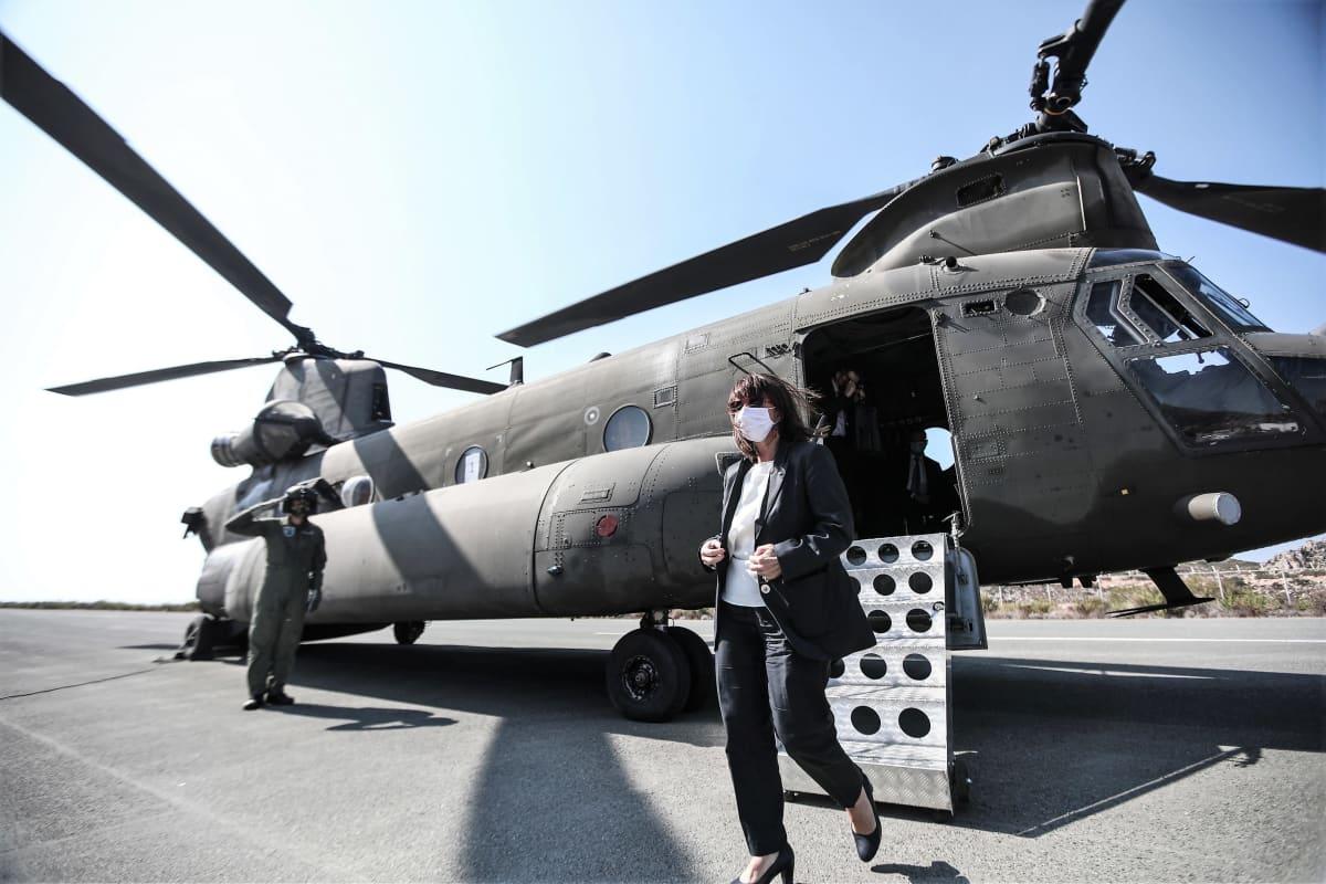 Kreikan presidentti Katerína Sakellaropoúlou on tulossa helikopterista. Hänellä on harmaa asu. Taustalla lentäjänasuinen kypäräpäinen mies vetää kättä lippaan presidentille.