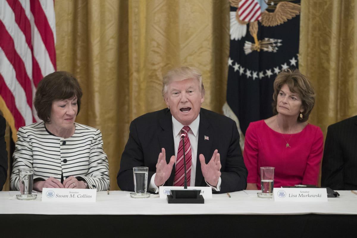 Susan Collins, Donald Trump ja Lisa Murkowski istuvat saman pöydän takana.