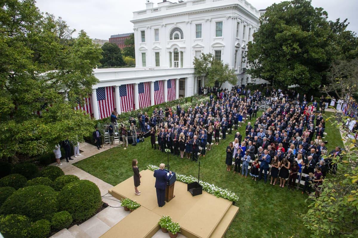 Yhdysvaltain presidentti Donald Trump puhuu tiiviisti istuvalle ihmisjoukolle Valkoisen talon pihalla.