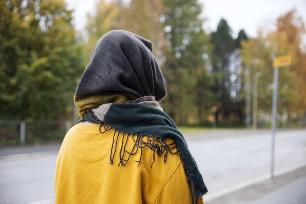 Tunnistamaton nainen kuvattuna takaapäin.