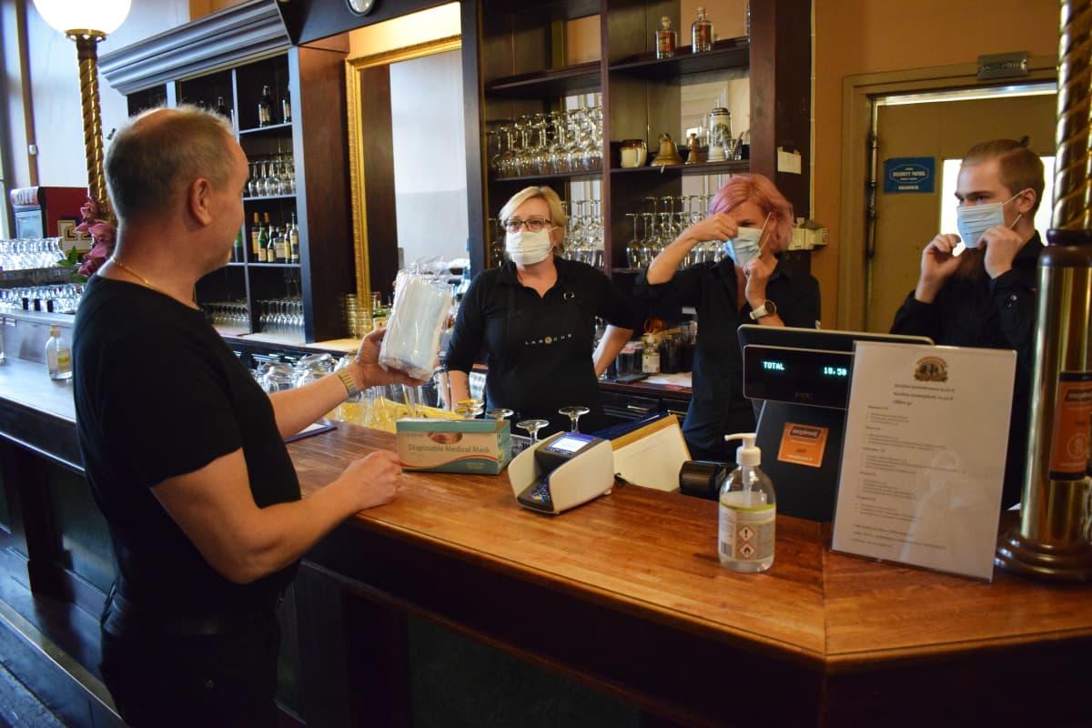Panimoravintola Koulun henkilökuntaa pukemassa maskeja.