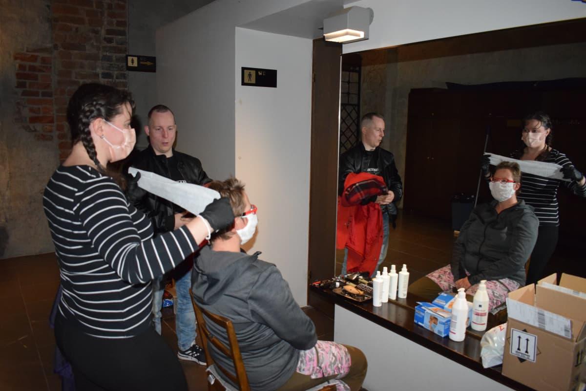 Nainen hiustenleikkuussa asunnottomien yössä.