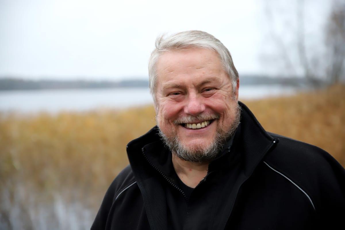 Tuomas Koskinen hymyilee kameralle, järvi taustalla.