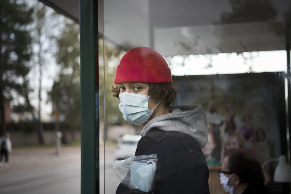 Kasvomaskiin pukeutunut henkilö seisoo bussipysäkillä.
