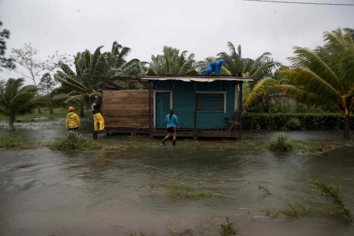 Ihmiset vahvistavat lautarakenteista kotia tulvavesien keskellä.