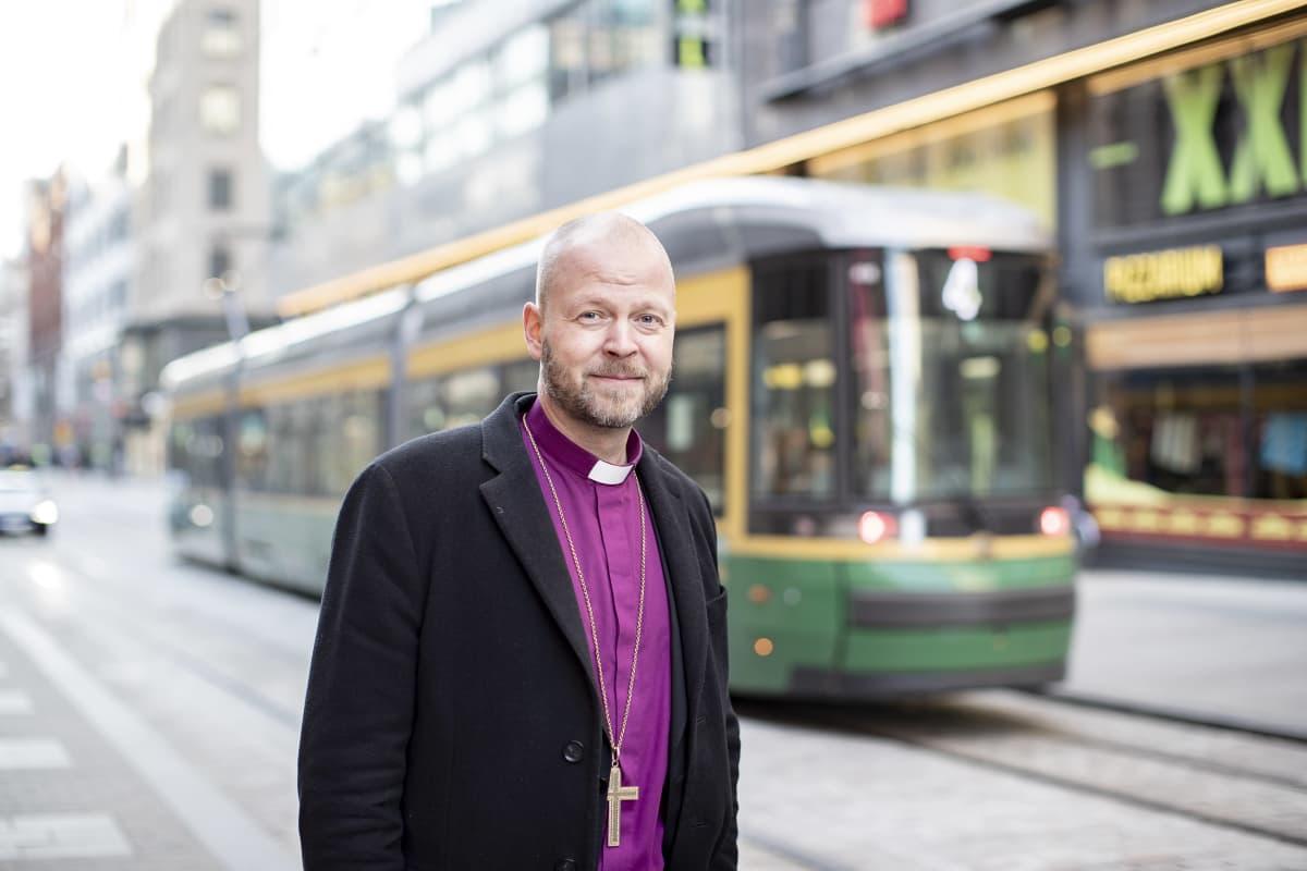 Piispa Teemu Laajasalo seisoo Helsingin keskustassa raitiovaunun edessä.