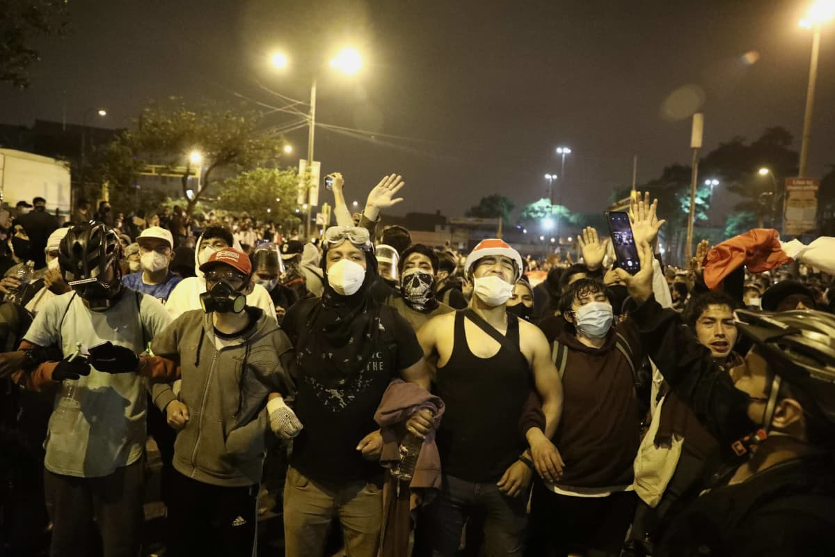 Kasvomaskeilla suojautuneita mielenosoittajia rivissä