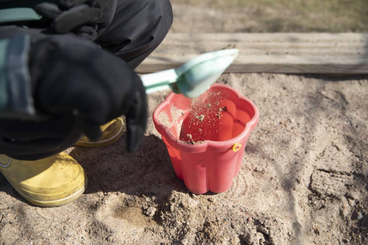 lapsi leikkii hiekkalaatikolla