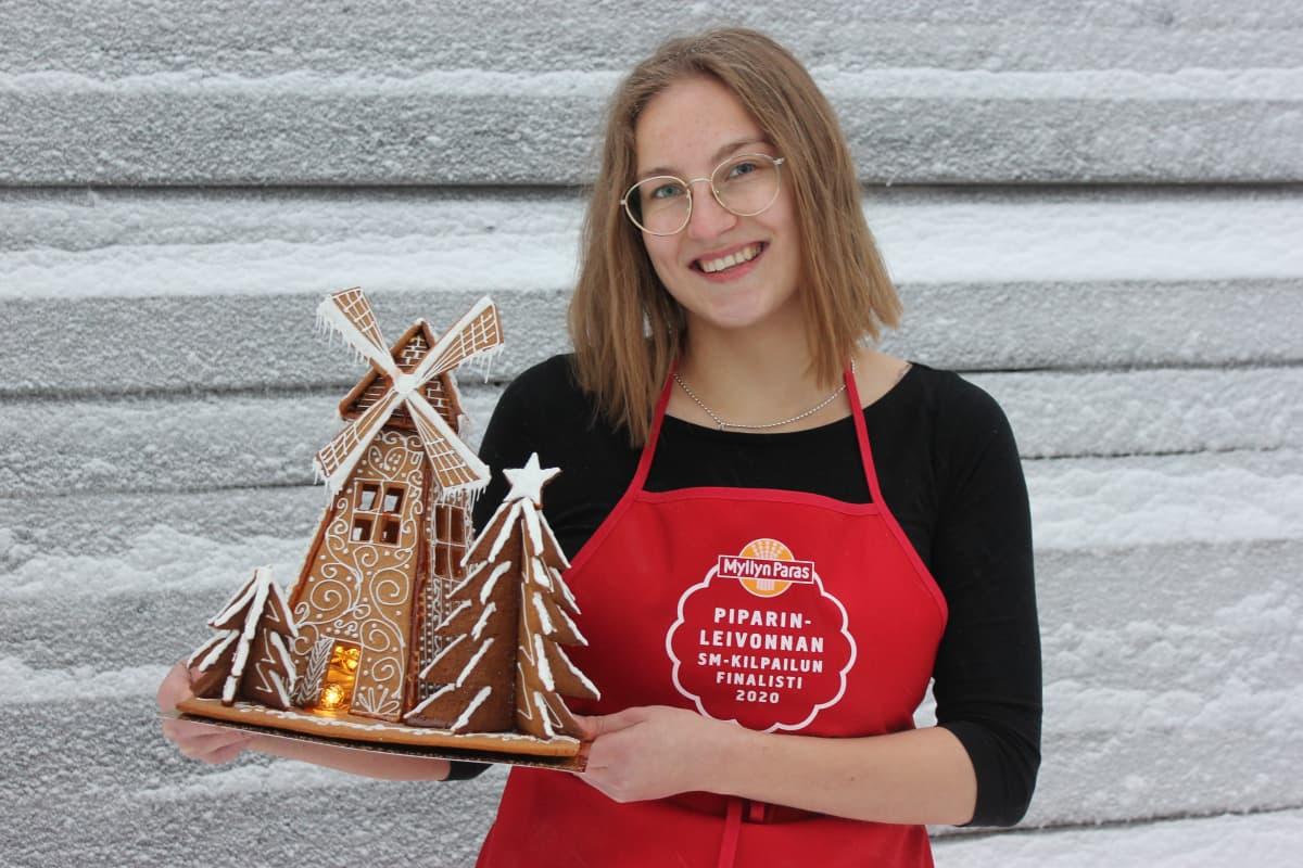 Piparinleivonnan SM-kisojen voittaja Maija Vuonokari hymyilee ja pitää sylissään voittajateostaan.