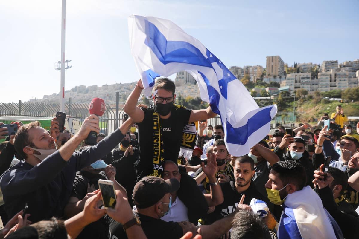 Beitar Jerusalem -joukkueen israelilaisomistaja Moshe Hogag kannattajien ympäröimänä.