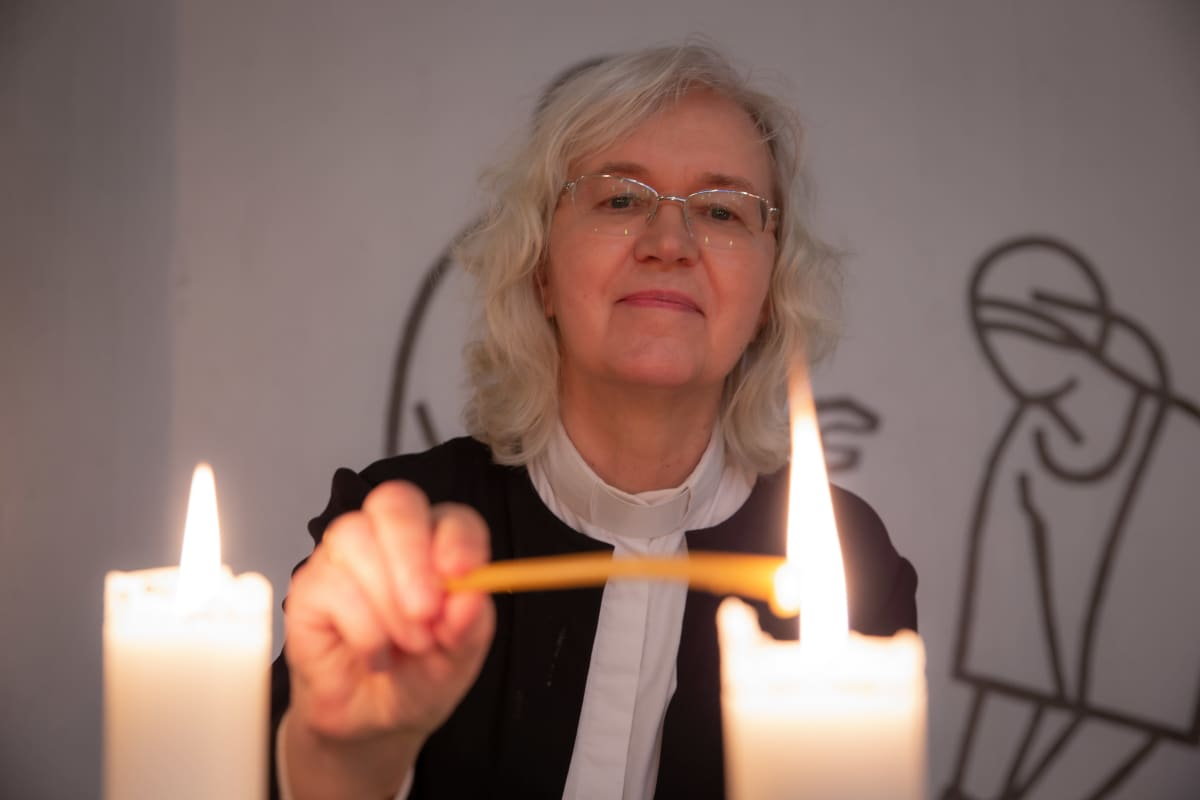 Kappalainen Marketta Antola sytyttää kynttilän Vuosaaren kirkossa.