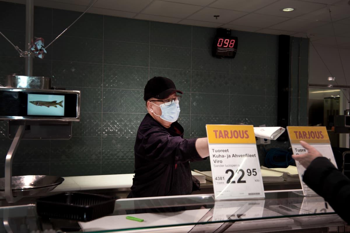 Jaakko Repo ojentaa kalapakettia asiakkaalle kaupan kalatiskillä.