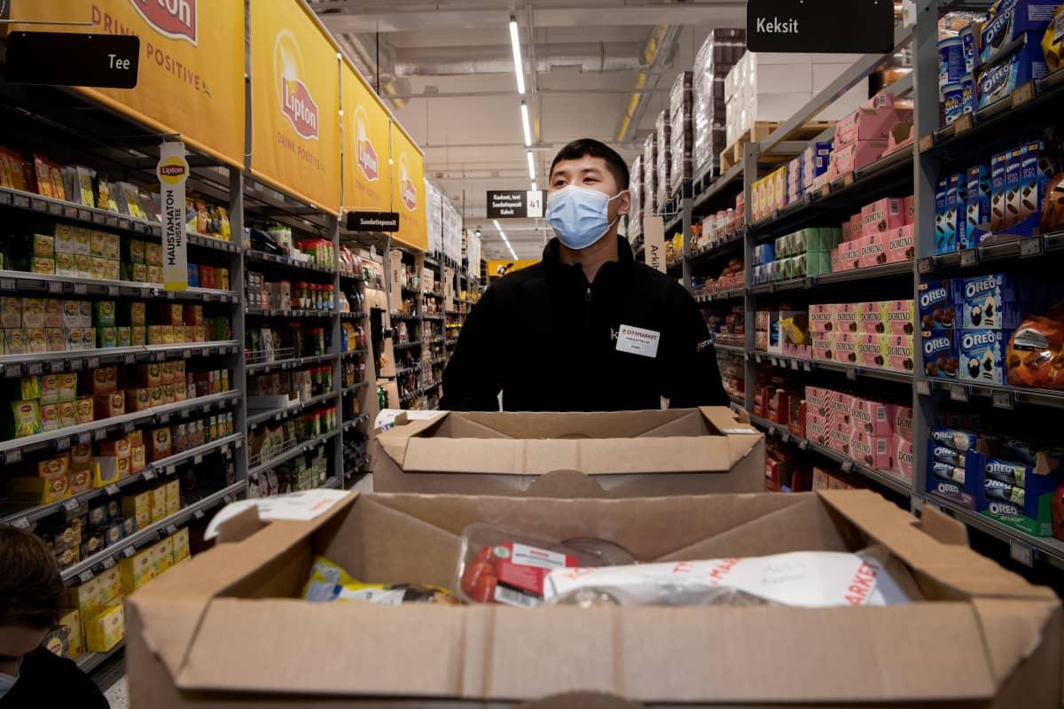 Dong Nguyen kerää ruokia pahvilaatikoihin ruokakaupassa.