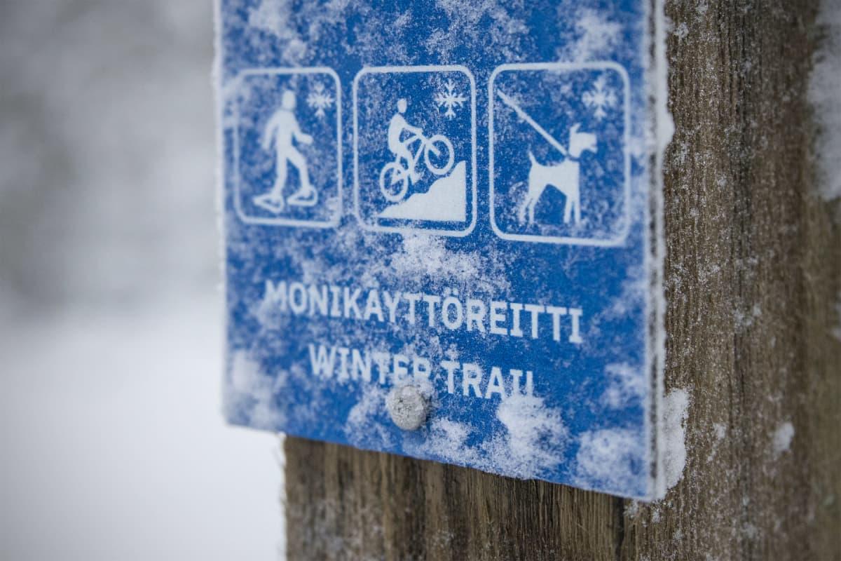 Monikäyttöreittien opaste, jossa lumikenkäilijän, maastopyöräilijän ja koiran kuvat.