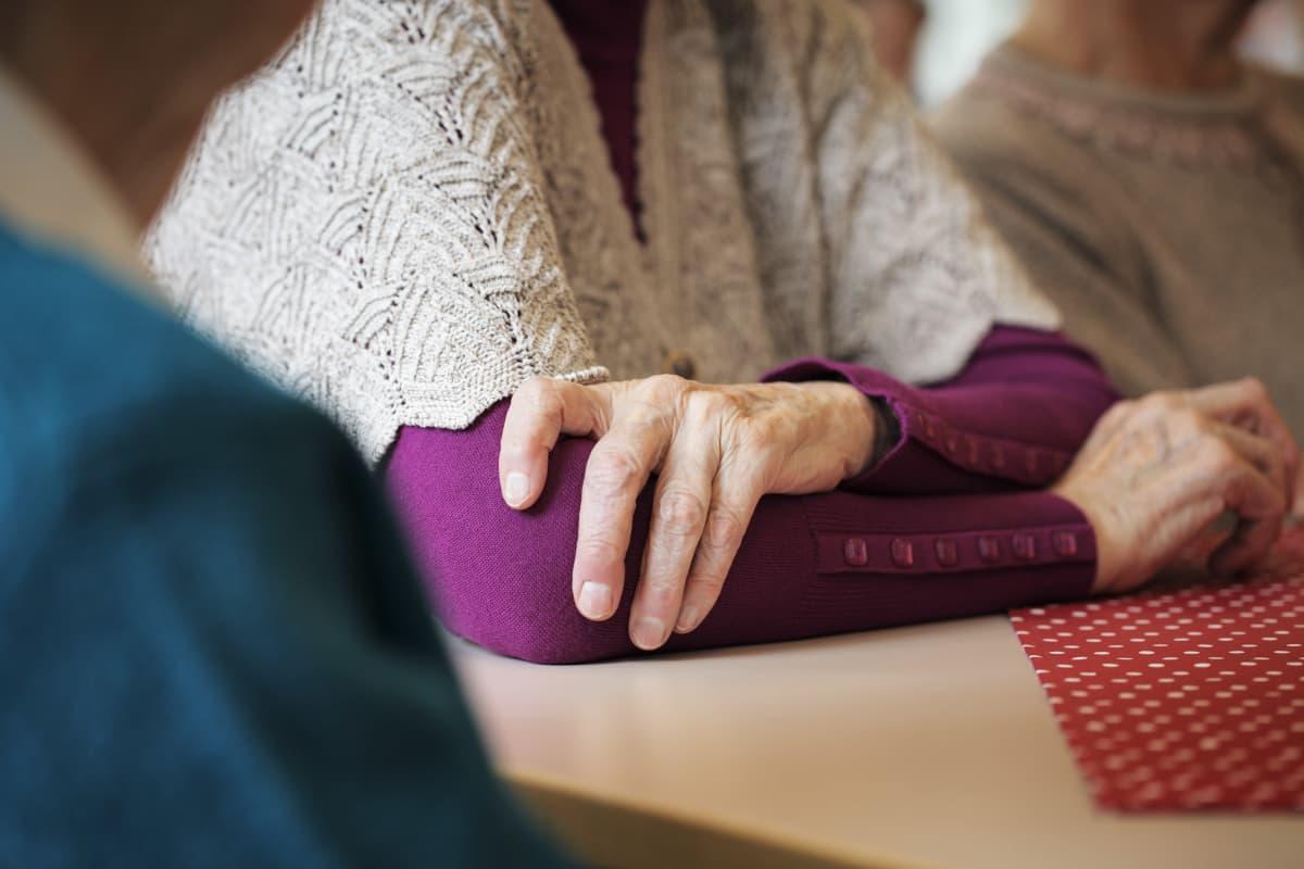 Gamla händer. Armar som lutar sig mot ett bord, lite med händerna i kors.