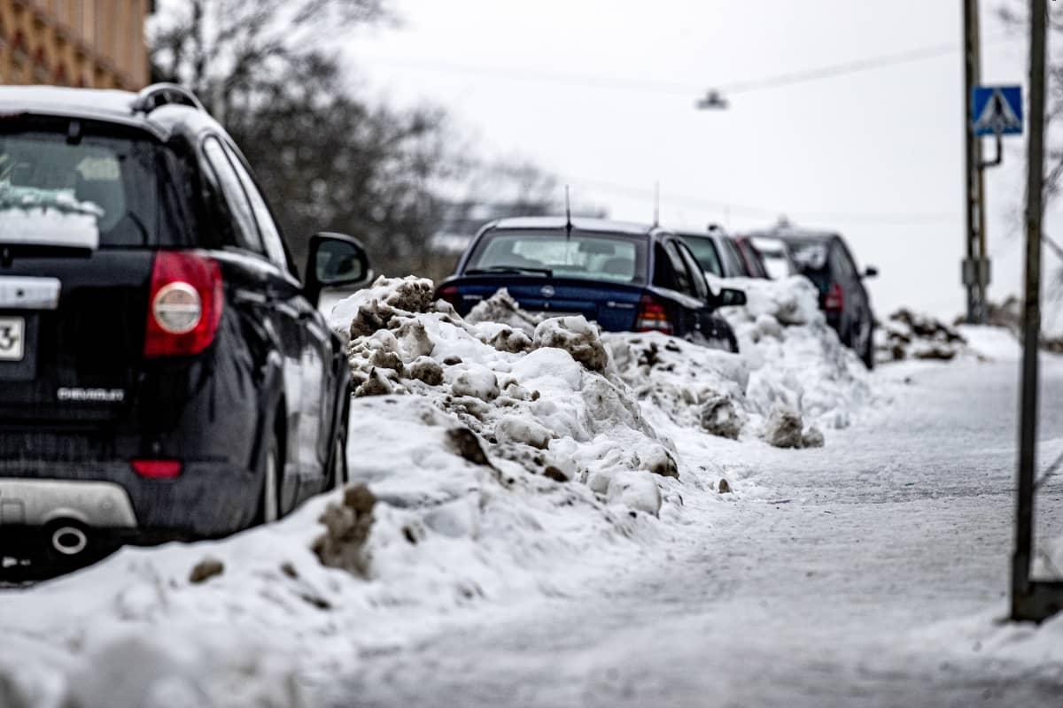 Katujen varsilla lumikasoissa olevia autoja.