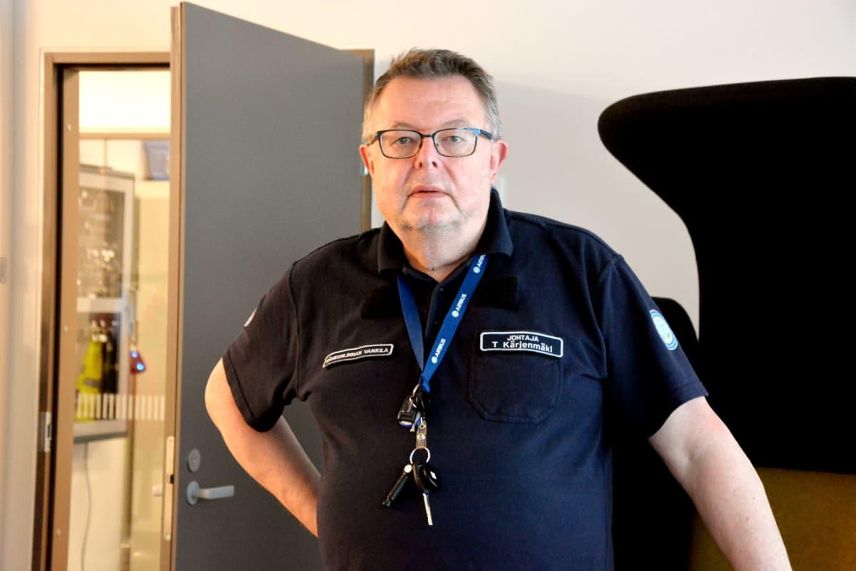 en man i mörk skjorta, nyckelknippa runt halsen och svarta glasögon står inomhus