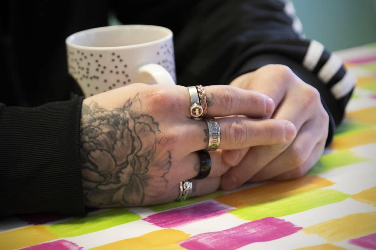 Tatuoidut kädet, joissa paljon sormuksia.