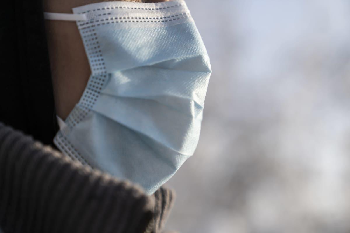 Anonyymi Rauhaniemen sairaalan lähihoitaja kuvattuna lumisessa metsässä kasvoillaan suojamaski..