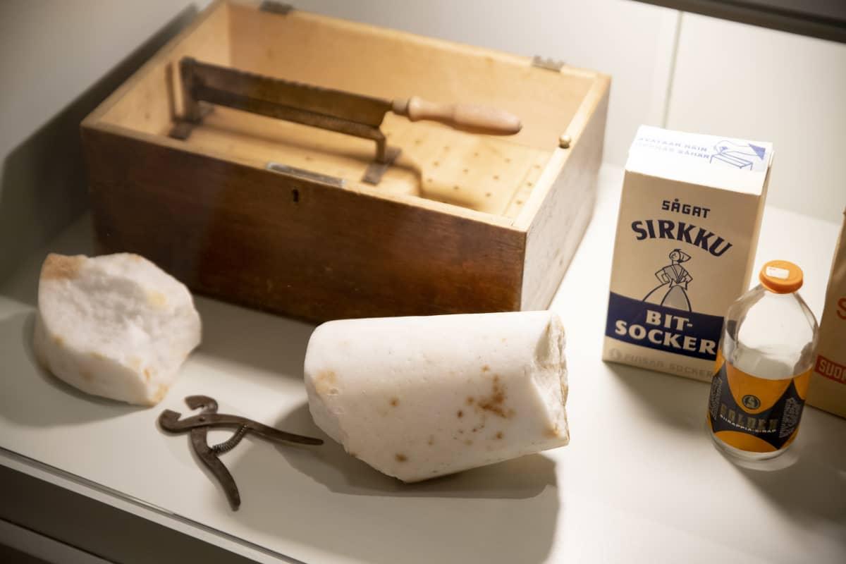 Lähikuva Sarka-museon näyttelystä: Sokerikimpale ja vanha sokeripaketti sekä tyhjä limsapullo.