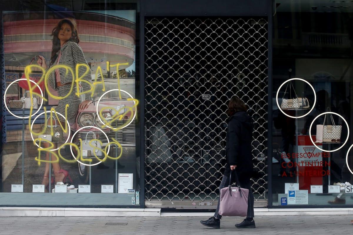 Ohikulkija tarkasteli mielenosoittajien kaupan ikkunaan töhertämää tekstiä maanantaina Barcelonan keskustassa.