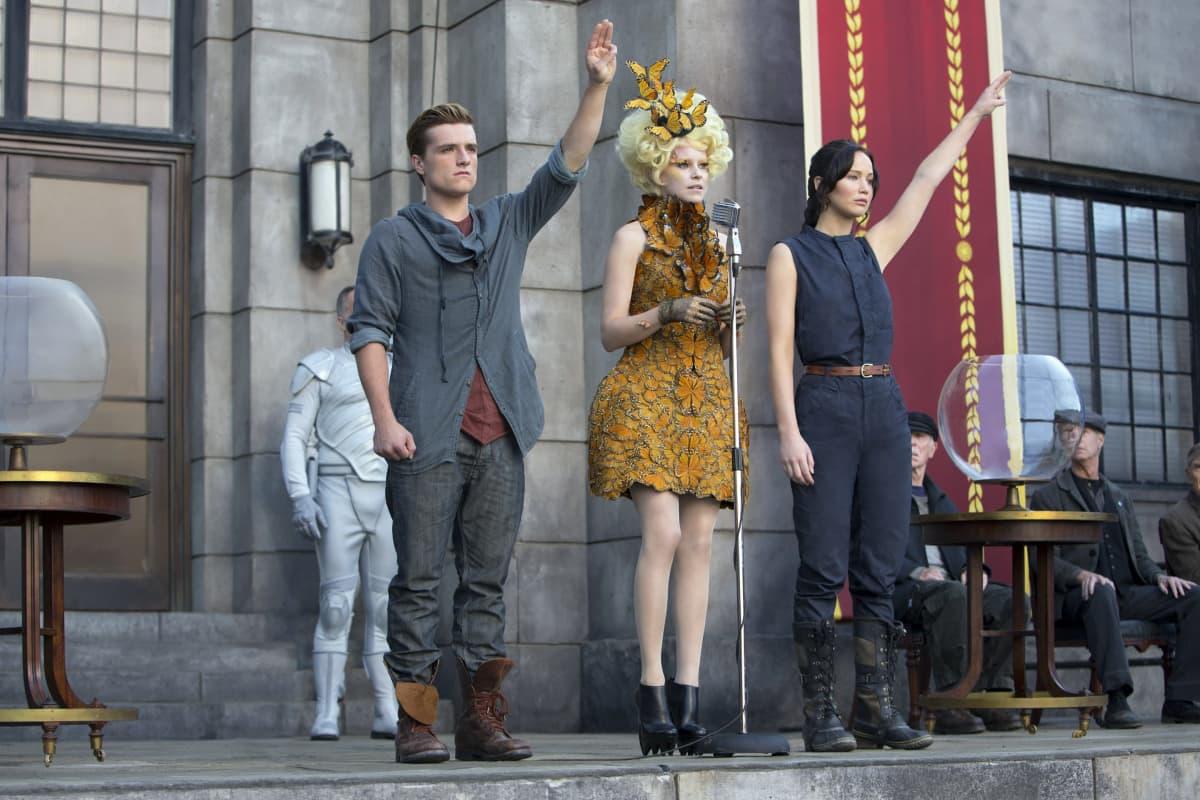 Kohtaus elokuvasta Nälkäpeli. Hahmot tervehtivät kolme sormea ylhäällä.