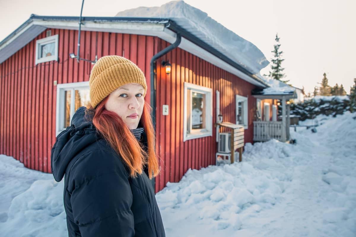 Anna Penttilä seisoo hometalon edessä.
