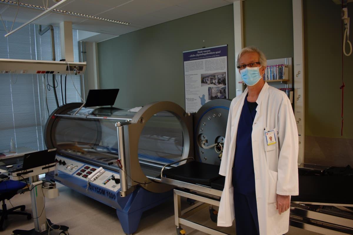 Teho-osaston ylilääkäri Mika Valtonen esittelee ylipainehappihoitolaitetta.