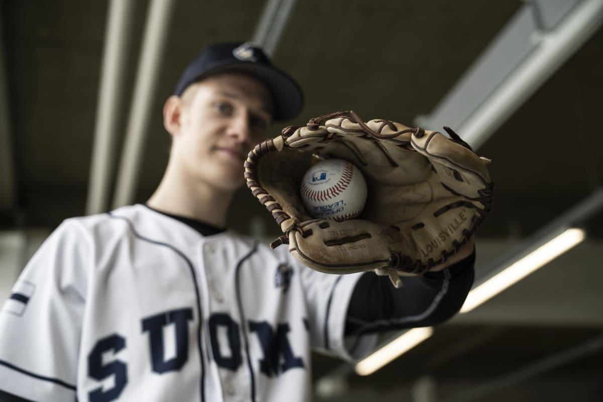 Suomalainen basebaal pelaaja Konsta Kurikka näyttää baseball palloa räpylä kädessä.
