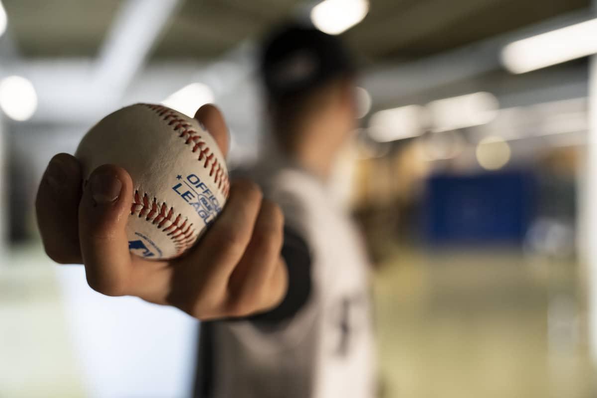 Suomalainen baseball pelaaja Konsta Kurikka heittää baseball palloa käsi taakse ojennettuna. Pallo etualalla juuri ennen heittoa.