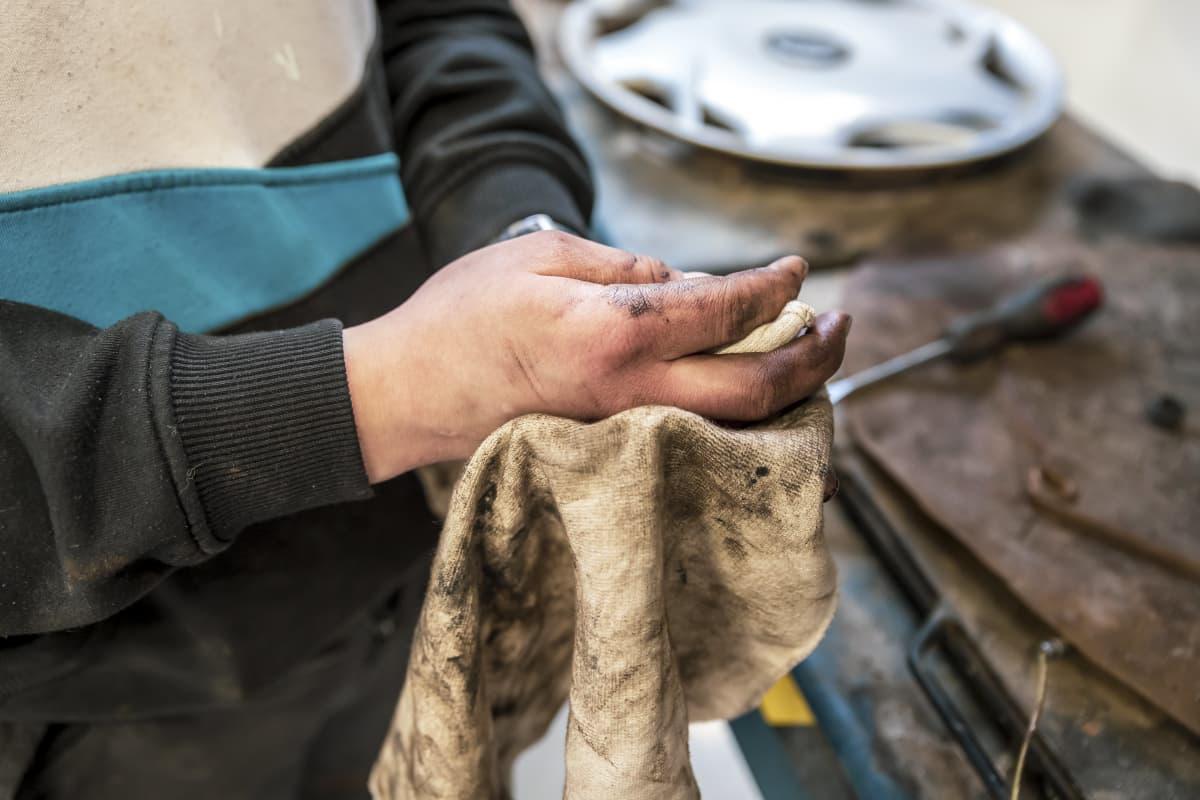 Oppilas pyyhkii likaisia käsiään rättiin.