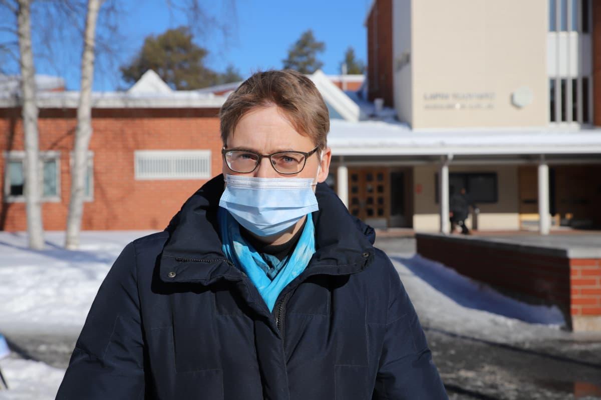 Lapin yliopiston rikosoikeuden professori Minna Kimpimäki katsoo kameraan maski kasvoillaan taustalla yliopiston päärakennus.