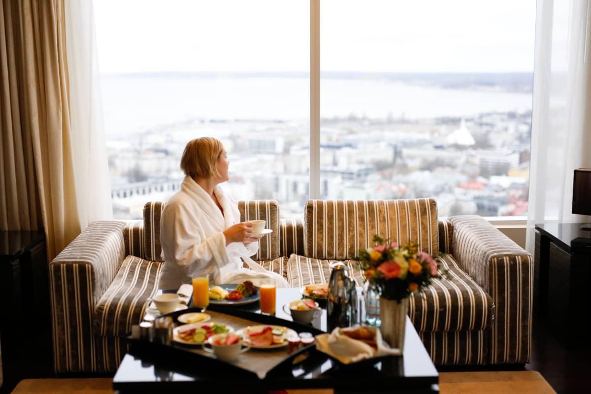 Nainen katselee hotellihuoneen ikkunasta ulos, kahvikuppi kädessä.