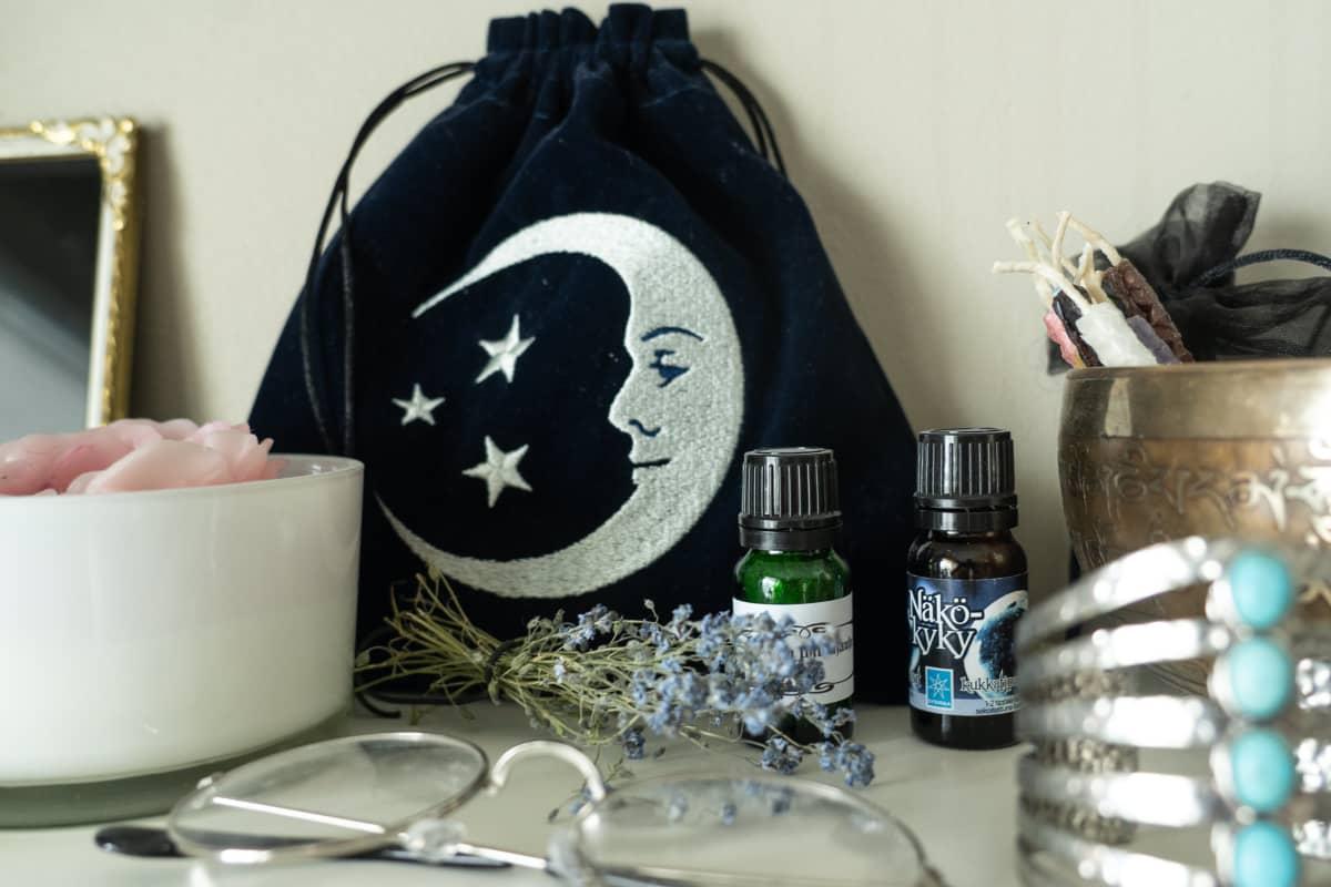 Nykynoidan hyllyssä olevia tavaroita: öljyjä, silmälasit ja kangaspussi, jossa on kuun kuva.