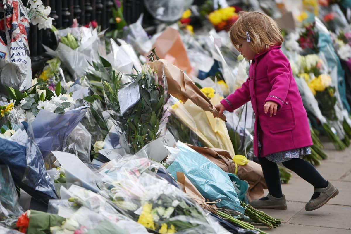 Tyttö jätti kukkakimpun Buckinghamin palatsin edustalle, jonne ihmiset ovat kerääntyneet muistamaan prinssi Philipiä.