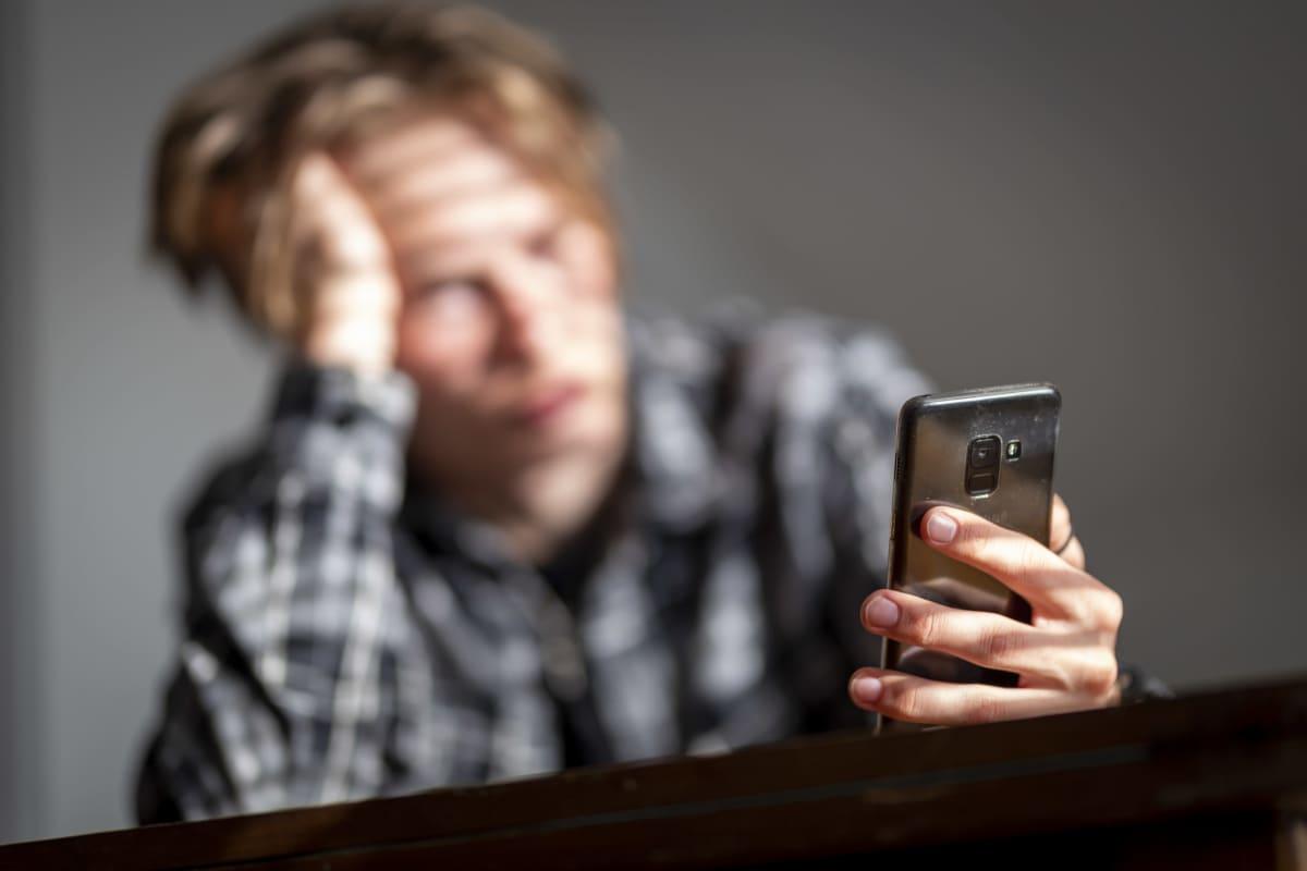 Tylsistynyt henkilö kännykkä kädessä.