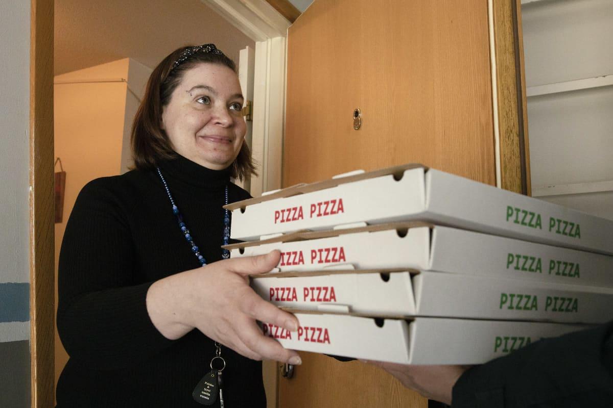 Hannele Pöysti ottaa vastaan neljä pitsalaatikkoa asuntonsa ovella.
