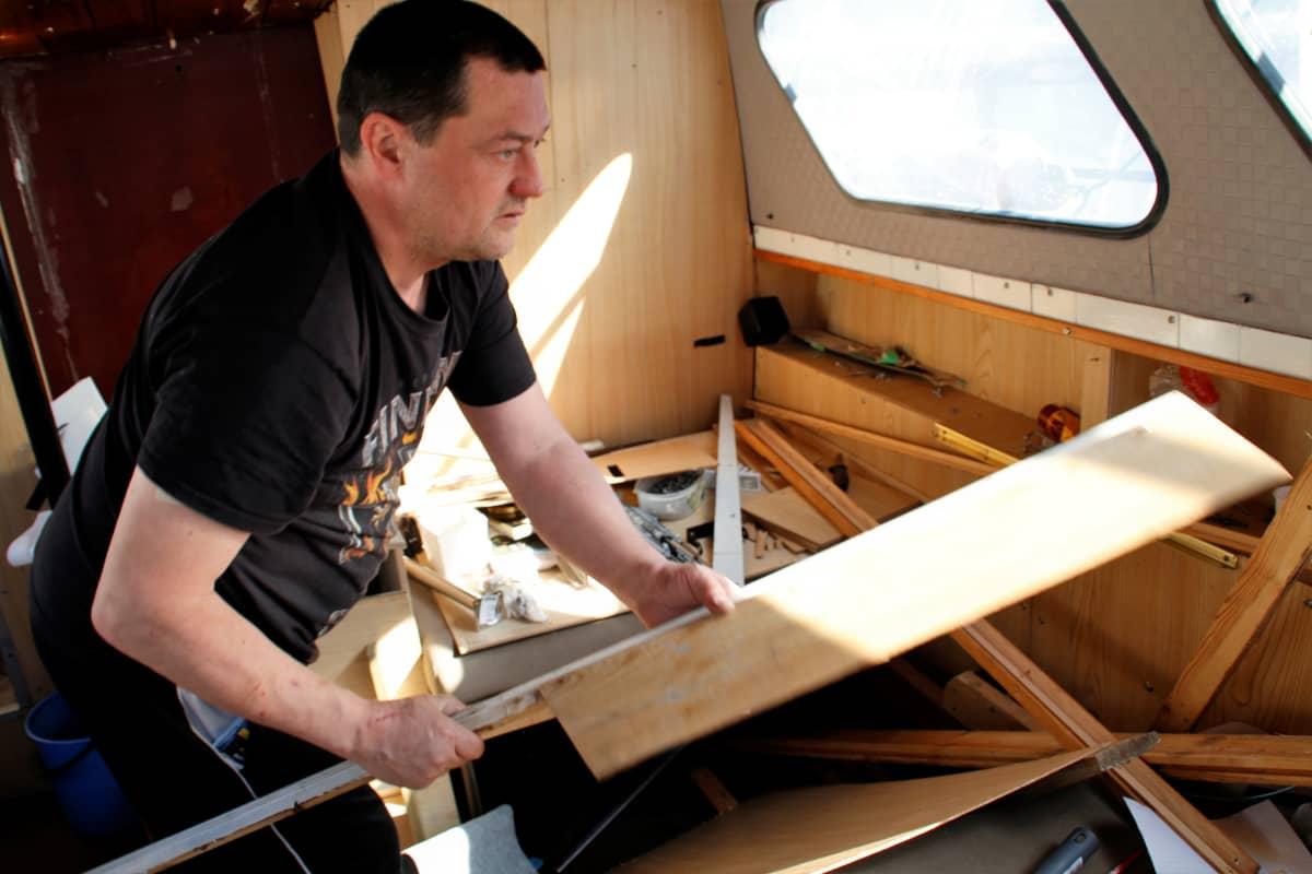 Kim Kukanaho siirtelee pöytälevyjä veneessään remontin keskellä