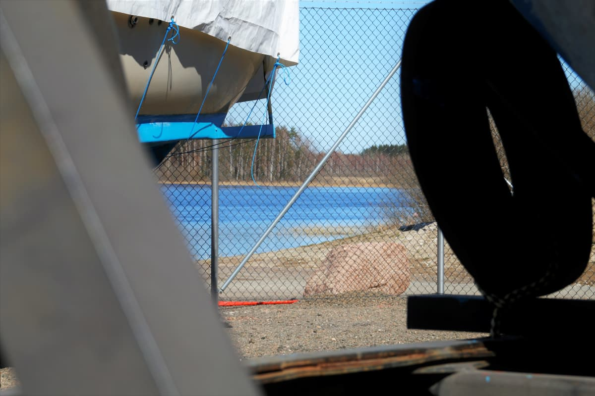 Vene talvisäilystyspukeilla Hirvelän venesatmassa Kouvolassa, taustalla Kymijoki