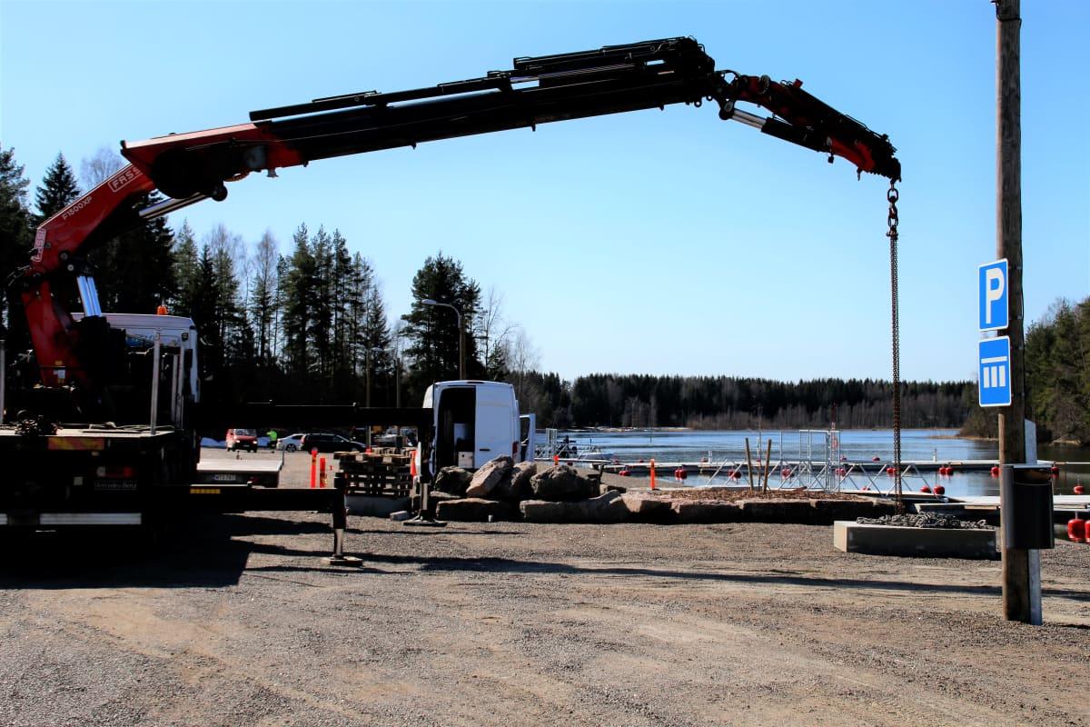 Nosturi töissä Hirvelän venesataman laiturialueella Kouvolassa Kymijoen rannassa